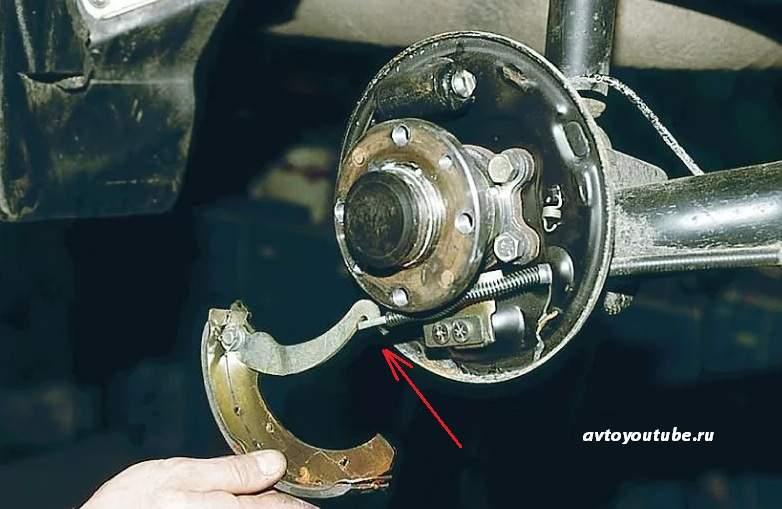 Надеваем рычаг ручника на ухо троса стояночного тормоза при замене задних тормозных колодок ВАЗ классика