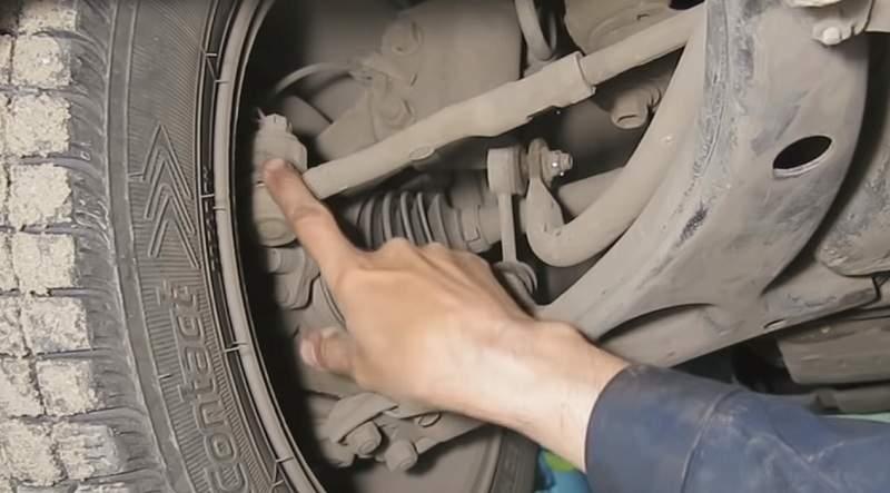 Для проверки люфта в шаровой опоре рулевого наконечника зажимаем его рукой и шатаем колесо рулем