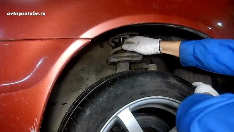 Проверка ступичного подшипника, держась одной рукой за пружину, второй вращая колесо