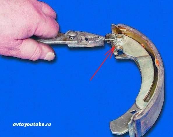 Расшплинтовываем рычаг стояночного тормоза и переносим его на новую заднюю тормозную колодку