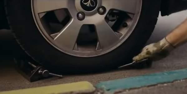 Подкладываем под колесо упоры, чтобы зафиксировать авто перед заменой поврежденного колеса